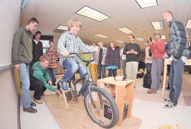 Strawberry Park Elementary School fifth-grader Trey Seymour tests out an energy bike prototype Tuesday at Steamboat Springs High School. Students at Strawberry Park and Soda Creek elementary schools are working with students in the high school's engineering club to produce four energy bikes that will power electronic devices.