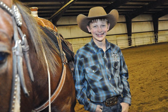 Kasen Brennise, 12, stands near his 9-year-old quarter horse Bart on Wednesday afternoon at an indoor arena near Craig where Kasen practices for rodeo events. Bart wears a trophy saddle Kasen won at a 2011 Little Britches Rodeo event in Rifle. The Craig Middle School sixth-grader also won the world champion barrel racer title at the 2008 National Finals Little Britches Rodeo.