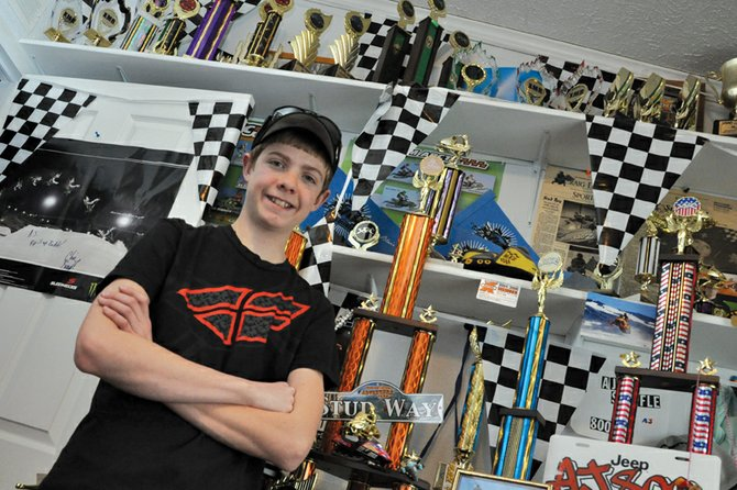 "A.J. Stoffle, 14, stands in his room packed with trophies he's won in snocross races. ""He eats and breathes snowmobiling,"" his mother Teresa Stoffle said."