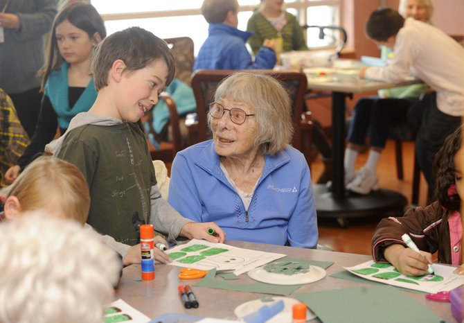 Strawberry Park Elementary School 7-year-old Will Cowman visits with 100-year-old Doak Walker Care Center resident Anna Wichern on Wednesday. Students from the school regularly visit the residents at the Doak.
