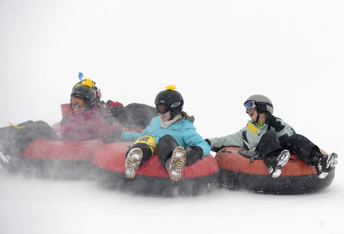 Sunshine Kids participants, from left, Emrene Sadek, 15, of Texas, Katie Darr, 17, of New York, and Tristan Hinshaw, 15, of Texas, ride down the tubing hill Thursday at Saddleback Ranch.