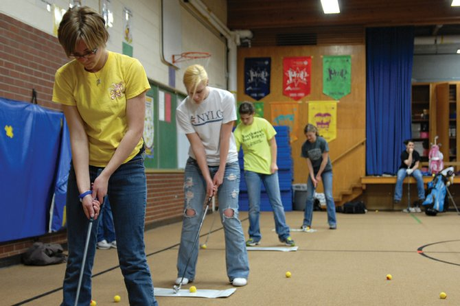 The Moffat County High School girls varsity golf team practices last week in the East Elementary School gymnasium. The Bulldogs competed in their first tournament of the season Monday at Chipeta Golf Course in Grand Junction. Head coach Ann Marie Roberts said despite the team not having practiced outside, each player made great strides.