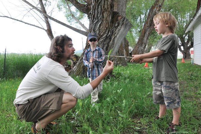Yampatika summer naturalist Kevin McGarity, left, holds out a leaf for Sam Kitchen to examine at Yampatika's Environmental Learning Center at Legacy Ranch in July. Steamboat Springs School District officials on Wednesday questioned the level of funding community groups like Yampatika receive from the Steamboat Springs Education Fund Board.