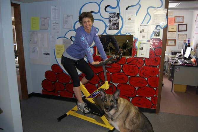 Barb Gregoire, owner of Trapper Fitness, hops on top of an exercise bike with her German shepherd, Tina, to keep her company. Gregoire, 56, is an advocate of staying fit through regular exercise and sensible eating, which she emphasizes to people who use Trapper's services.