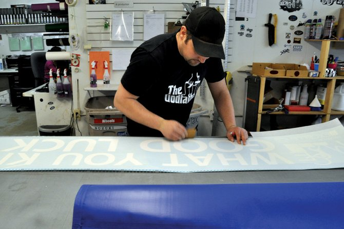 Identity Graphics owner Joel Browning prepares vinyl letters Tuesday for a banner encouraging students to perform well on the Transitional Colorado Assessment Program, an amended version of the Colorado Student Assessment program. Maximum Commitment to Excellence, a local grassroots group, is spearheading an effort to get local entrepreneurs to display the banners and signs at their businesses.