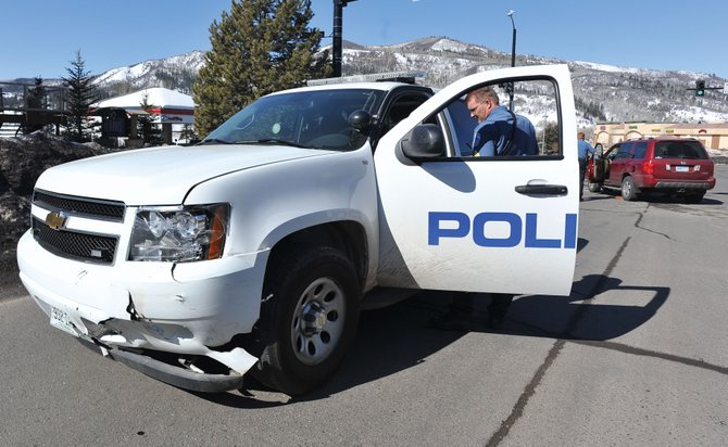 Steamboat police Sgt. Gerard Geis walks around his patrol car, which was involved in an accident at Mount Werner Road and Central Park Drive on Wednesday morning. The police car collided with a Honda Pilot, shown in the background, while attempting to make a left turn onto Mount Werner Road. Two people in the Pilot were transported to Yampa Valley Medical Center with minor injuries.