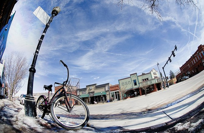 A bike sits in front of a light post Friday morning in downtown Steamboat Springs. Tracy Barnett, of Mainstreet Steamboat, is looking for feedback about an idea to claim some parking spaces downtown for bike racks, like some other communities, instead of forcing people to use light poles and tree trunks.
