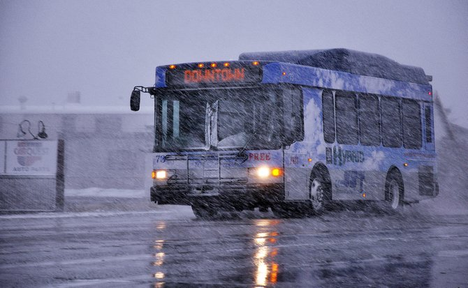 A Steamboat Springs Transit bus drives through wind and snow Sunday near the intersection of U.S. Highway 40 and Routt County Road 129. One of the city's hybrid diesel buses will be on display Monday in the Depot Art Center parking lot during an expo showcasing vehicles that utilize alternative fuels.