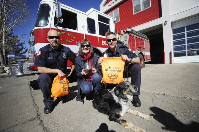 Steamboat resident Mindy Falzarano holds one of the animal oxygen masks she recently donated to Steamboat Springs Fire Rescue. Also pictured are Lt. Michael Arce, left, firefighter Scott Hetrick and Everest the dog.