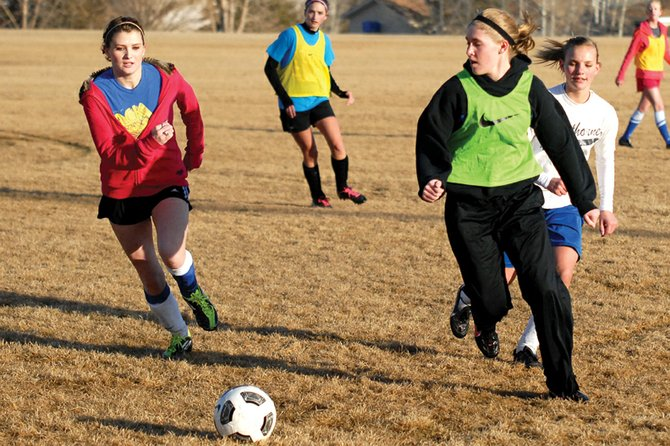 Kelsie Pomeroy, center right, a Moffat County High School junior, pushes the ball downfield past defenders March 7 outside MCHS. Pomeroy and senior Kelly Ciesco return from last season to help lead the MCHS girls varsity soccer team's offense this year.