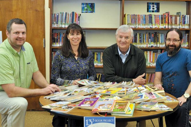 Members of the newly formed Friends of Moffat County Education pose for a photo Thursday in the Sandrock Elementary School library. The group recently obtained its nonprofit status from the Internal Revenue Service and is launching its first project, a book drive designed to gather 13,000 books for local children. Pictured, from left, are board president Chris Jones and members Michele Chalmers, Bill Lawrence and Jeremy Browning.