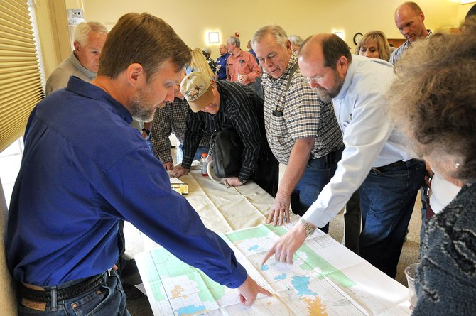 Matt Holman, left, points to Shell Oil's proposed drilling sites on a map of Routt and Moffat counties Tuesday night in Hayden. Holman is Shell Oil's exploration project manager for this area.