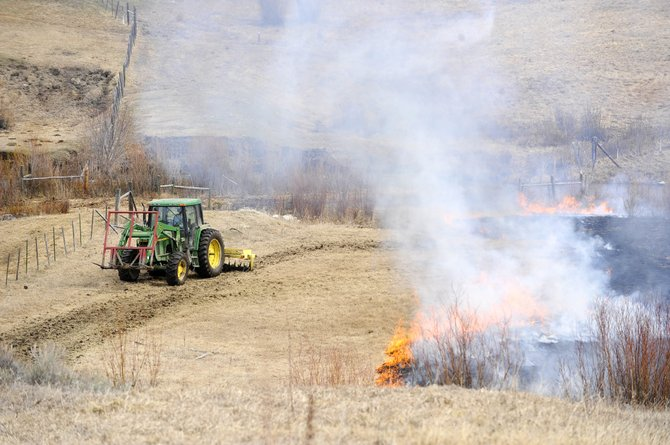 A tractor is used to help stop a wildfire that started when a controlled burn got out of control Friday morning at a ranch along Routt County Road 37D in southwest Routt County.