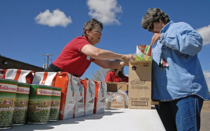 Becki Miller, left, a volunteer and front desk administrator for the Boys & Girls Club of Craig, helps disburse food during the Food Bank of the Rockies' first mobile food pantry distribution in Craig. Starlene Collins, Western Slope Manager for FBR, said the agency plans on having a mobile food pantry distribution every month at the Boys & Girls Club of Craig, 1324 E. Highway 40.