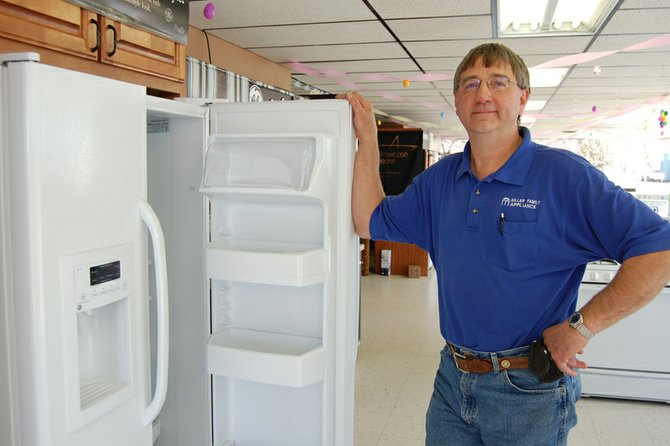 Chris Miller is shown with a refrigerator on the sales floor of his business, Miller Family Appliance. Miller, 53, is a father of five and has owned his store since 2005.