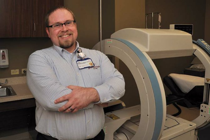 Eric Zalusky, diagnostic imaging manager at The Memorial Hospital, stands next to the hospital's nuclear medicine camera Monday morning. The hospital board gave the green light Thursday to purchasing a new machine with a dual-head camera, which should reduce procedure times by about half, he said.