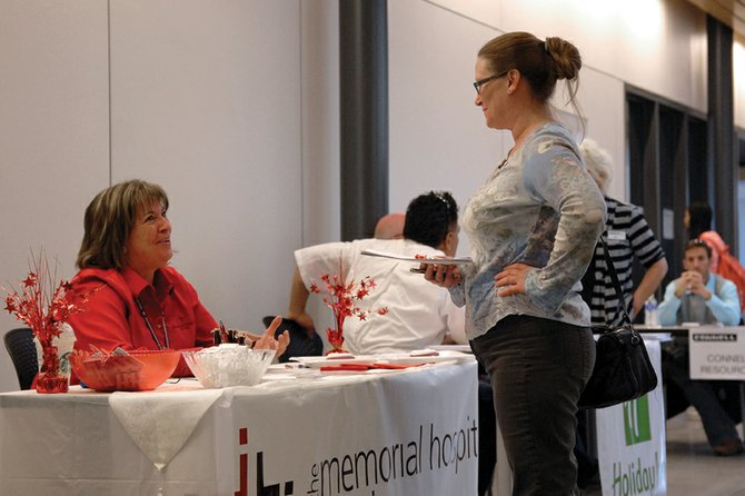 A visitor to the 2012 Moffat County Job Fair stops at The Memorial Hospital's booth Friday at Colorado Northwestern Community College's Craig campus. More than 150 potential employees visited the fair, which featured booths from 19 employers.