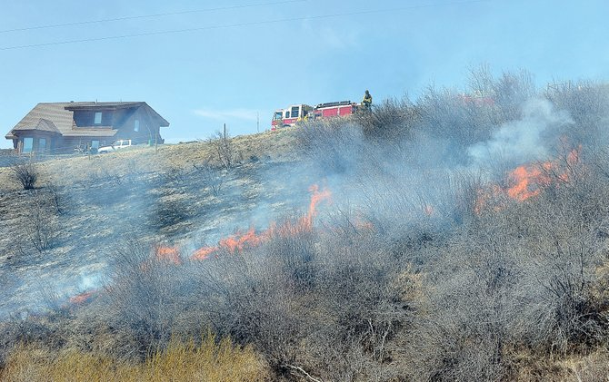 A line of flames consume grass near a home at the intersection of Routt County Road 46 and Fawn Creek Road. Steamboat Fire Rescue responded to the fire but ended up watching as the fire burned itself out.