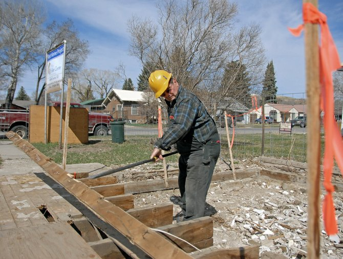 Neil Folks, president of the Moffat County Fuller Center for Housing, pulls floor boards Wednesday from a condemned structure at 731 Yampa Ave. Once rebuilt, the new structure will be repurposed for low-income housing. The Fuller Center needs volunteers to continue the project. A volunteer work weekend is scheduled for 9 a.m. to 6 p.m. April 14 and 15. For more information, call Folks at 326-8726.