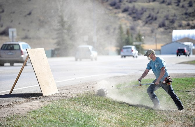 Routt County employee Tim McDonald uses a power broom Thursday morning to clean rocks and other roadside debris out of the lawn between the Routt County Jail and U.S. Highway 40. This year's unseasonably high temperatures have allowed spring cleaning to begin early in the Yampa Valley, but they also have brought dry conditions along with red flag warnings.