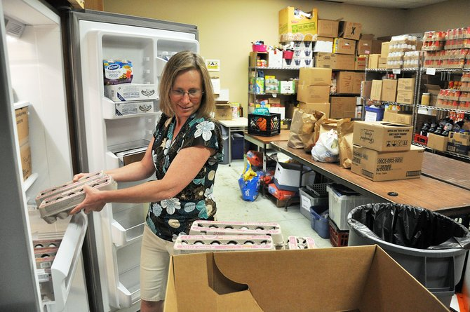 LIFT-UP of Routt County food bank volunteer Elizabeth Black takes eggs out of a new refrigerator Thursday that was paid for by an Energy Outreach Colorado grant. LIFT-UP was one of two Routt County nonprofits that recently received energy efficiency upgrades through the state program.