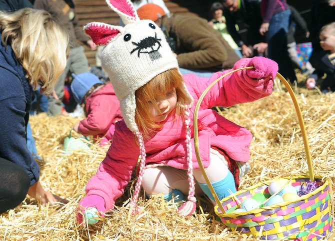 Ellie Hunt, 2, reaches to deposit an egg in her basket Saturday at the Steamboat Christian Center's Eggstravaganza Easter egg hunt. The event drew a huge crowd of children and plenty of adults to help dig through the hay to find the wealth of eggs.