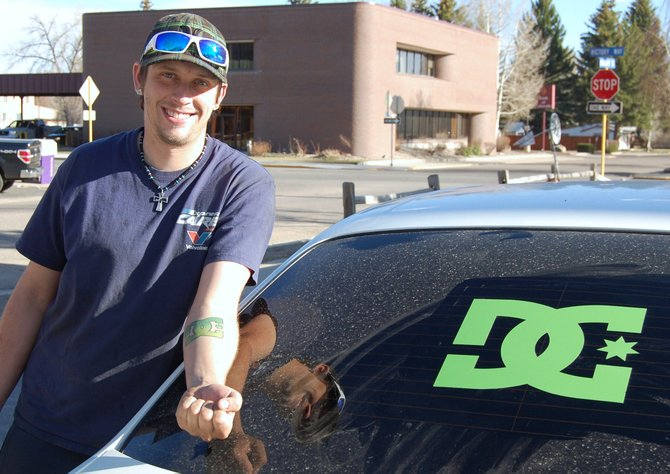 Kenny Cooper displays his forearm tattoo of the DC Shoes logo, which matches the decal on the rear window of his car. Cooper, 26, has worked at Lube Plus since about 2010 and has enjoyed working on cars for even longer.