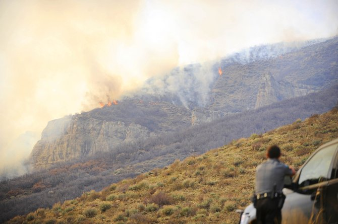 Routt County Sheriff's Office Sgt. Doug Scherar watches Tuesday as a wildfire spreads at a ranch along Routt County Road 31 in the southern part of the county. Sheriff Garrett Wiggins estimated the fire had burned 200 acres and was not under control as of Tuesday evening.