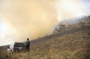 Routt County Sheriff's Office Sgt. Doug Scherar watches Tuesday as a wildfire spreads at a ranch along Routt County Road 31 in southern Routt County.