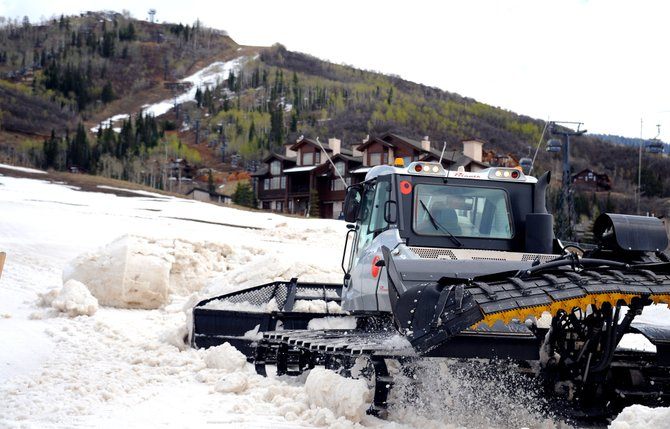 A snowcat pushes a pile of snow around the base area at Steamboat Ski Area on Friday. Pushing piles of snow isnt the most efficient way to handle it, but it was the only option this spring as a dry season and warm weather combined to test ski area slope maintenance crews. They managed to keep the mountain open to its planned Closing Day.