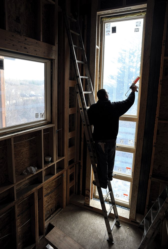 Carlos Luna caulks around the window of a home being renovated by PureBuilt Inc. near Fish Creek Falls. The home is being completely redone, and its owners are looking into ways to make the home more efficient and sustainable for the future.