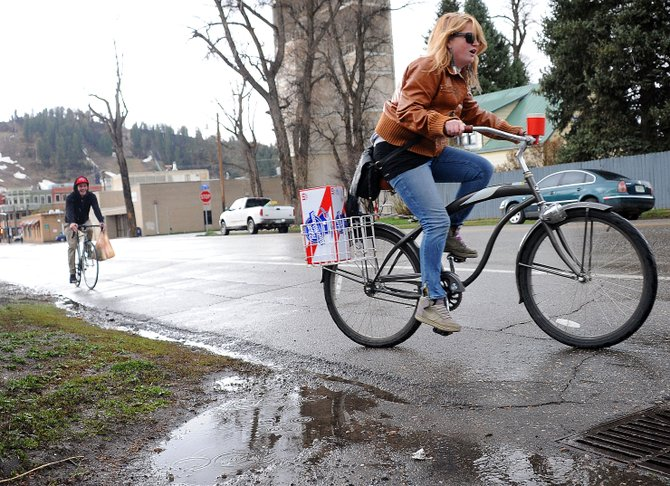 Mel LeBlanc and James Mowatt pedal home with all the ingredients for a night in Thursday afternoon after a quick downtown shopping trip in Steamboat Springs. Intermittent bands of rain and hail swept across Steamboat on Thursday, but the weekend looks sunny.