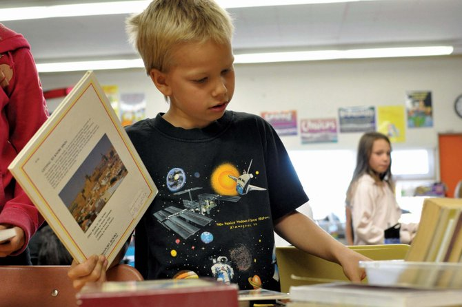 Garrett Bowersox looks through a pile of books in Adrienne Burch's third-grade classroom at East Elementary School. Burch's students were tasked with determining whether a book was fact or fiction, a skill they would use during a three-week research project about Craig history.