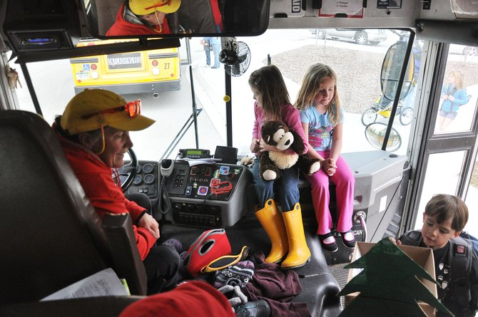 School bus driver Bethany Aurin welcomes Grey Barbier aboard a bus Thursday at Soda Creek Elementary School as kindergarten classmates Berit Baker, left, and Anna Becker wait on the dashboard. Routt County school districts have been weighing changes to their school calendars.