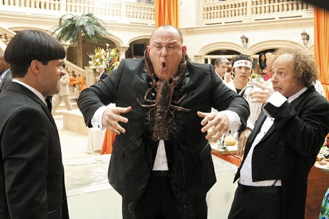 "Curly (Will Sasso) finds himself on the wrong end of a seafood dinner at a high society function, much to the amusement of pals Moe (Chris Diamantopoulos) and Larry (Sean Hayes) in ""The Three Stooges."" The movie is a recreation of the classic comedy team, focusing on the Stooges as they set out to save their childhood orphanage."
