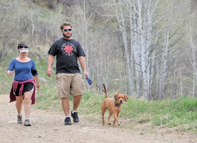 Kyle Love, right, and Maria Palmer walk Brewster along the Spring Creek Trail on Thursday afternoon. Love and Palmer say they always pick up after Brewster, but that cant be said of all dog owners. Thats why organizers of April Stools Day are hoping that a large number of volunteers will come out in force Saturday to help clean up local parks and trails across Steamboat Springs.