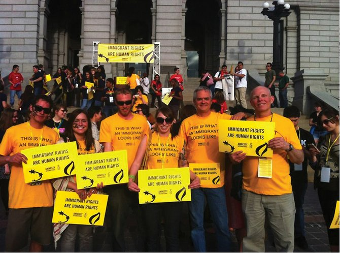 Local Amnesty International chapter members, including, from left, Kyle Hornor, Ashley Carson, Chris Jiggens, Molly Goldberg, Bob Gumbrecht and Larry Haines, recently attended a protest in Denver to advocate immigrant rights. The groups are holding a fundraiser at 7 p.m. Thursday at The Tugboat Grill & Pub.