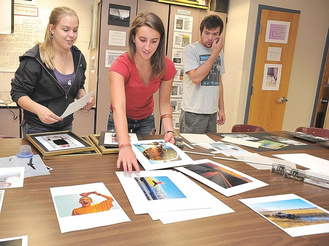 Photography students Dani Perry, right, and Haley Orton look through images while preparing for First Friday Artwalk. The students' photographs will be displayed at City Cafe during May.