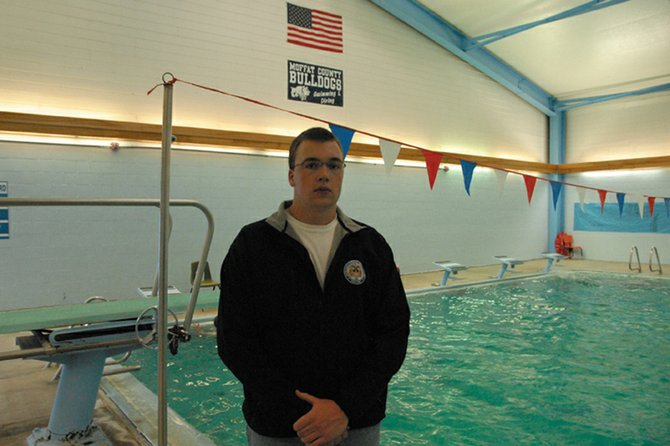 Moffat County High School senior John Kirk stands proudly beneath the American flag at the MCHS pool. Kirk, the captain of the boys varsity swim team, will be attending the United States Merchant Marine Academy in the fall, where he will row crew for the military institute. The jacket he is wearing has the USMMA insignia on the front.