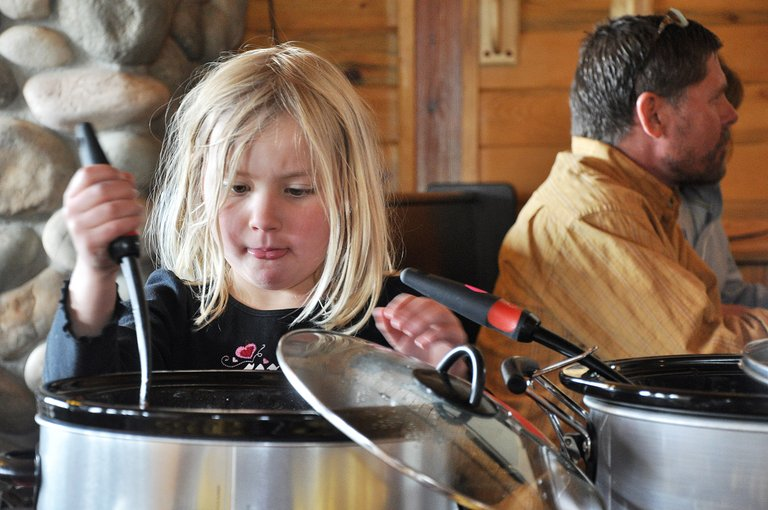 Sydney Lotz reaches in for a ladle of chili Sunday at the 10th annual Great North Routt Chili Cook-Off at Hahn's Peak Roadhouse.