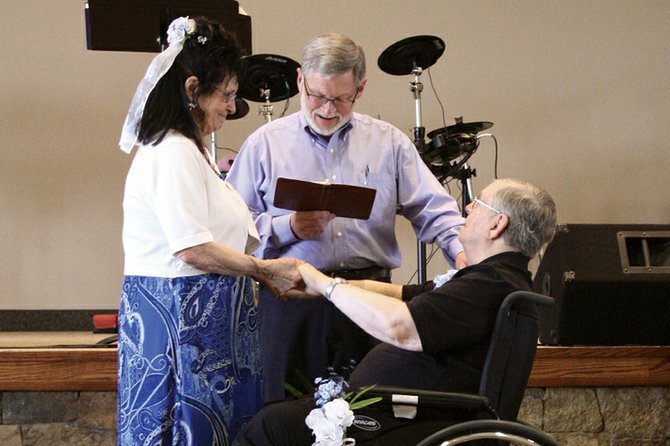 Frank and Barbara Jean Sonntag clasp hands as Dan Canady, former pastor of The Journey at First Baptist, officiates the renewing of their vows Sunday at the church. The couple reunited in 2011 after more than 15 years of separation.