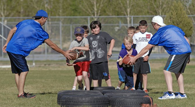 A pair of Moffat County elementary school kids charge the tires Wednesday during a running back drill at the Moffat County High School practice field. According to organizers, the hallmark of the eighth annual Big Blue Football Camp is to teach children football fundamentals in a safe and fun environment.