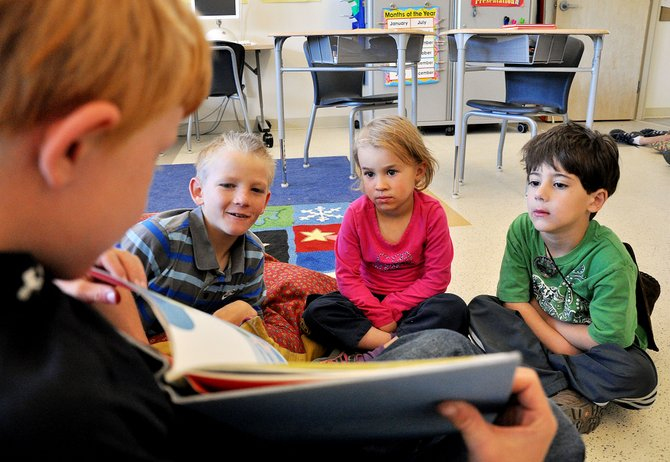 North Routt Charter School student Emmitt Meyring holds up a book as Lex Lewis, left, reads with North Routt Preschool students Emma Crocker and Sal Bessey. Collaboration between students at the two campuses is easier now that their buildings neighbor each other.