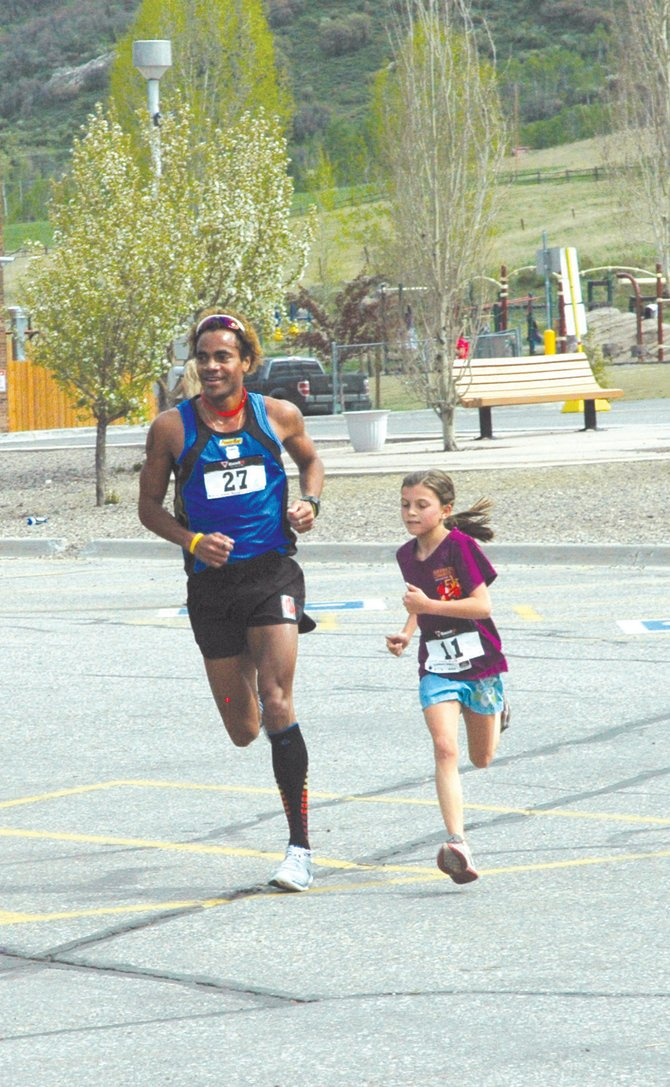 Roberto Mandje helps a young participant across the finish line Saturday at the 2012 Spirit Challenge. Mandje was in town between training for the 1,500-meter event at the 2012 London Olympics.