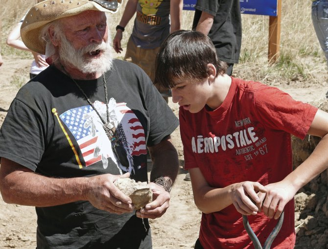 Jan Roth, left, of the Sundance Research Institute, explains to Steamboat Springs High School sophomore Nick Vaughan how to identify the different types of fossilized plants discovered in rocks excavated from a potential Columbian mammoth site in Craig. The first day of the dig did not yield any mammoth remains, but Roth was encouraged by plant fossils and another discovery of what could be a hearth site.