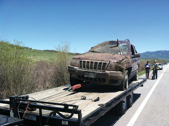 Colorado State Patrol troopers investigate the scene of a rollover crash that sent two people to the hospital at about 11 a.m. Monday on Colorado Highway 131. 