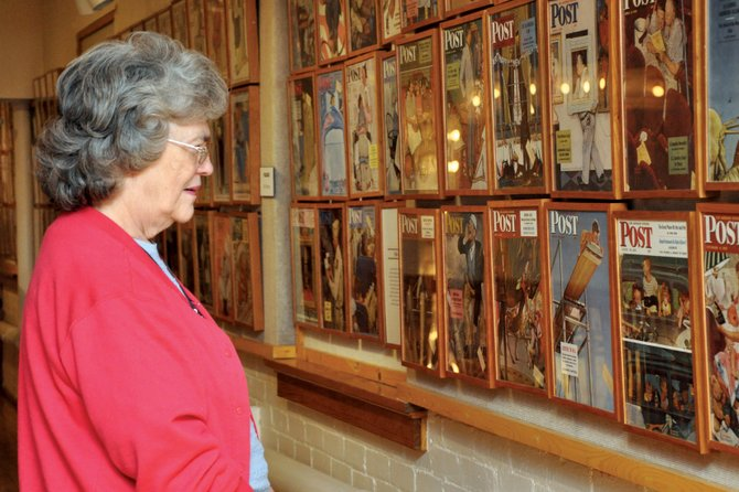 Anne Carr, of Craig, looks at an exhibit Monday at the Museum of Northwest Colorado that features all 323 Saturday Evening Post covers illustrated by Norman Rockwell. The exhibit opened Monday and has garnered interest in and beyond Craig, museum staffers said.