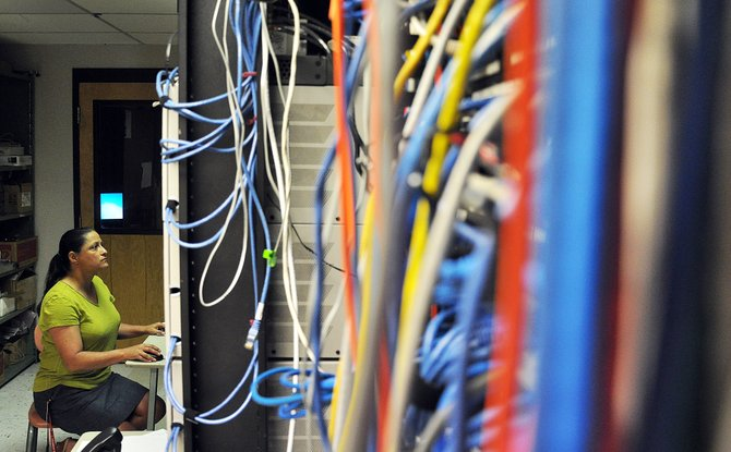 Kandise Gilbertson, a technology integration specialist for the Steamboat Springs School District, performs some maintenance on security cameras Tuesday from the data center inside Steamboat Springs Middle School. The South Routt School District is planning to consolidate its technology resources with Steamboat.