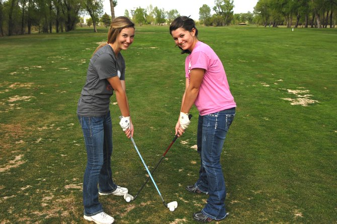 Moffat County High School sophomore Caitlin Harjes, left, and senior Sam Fox cross their clubs on a fairway at Yampa Valley Golf Course. The two members of the girls varsity golf team will play in the 4A state tournament Monday and Tuesday in Greeley.