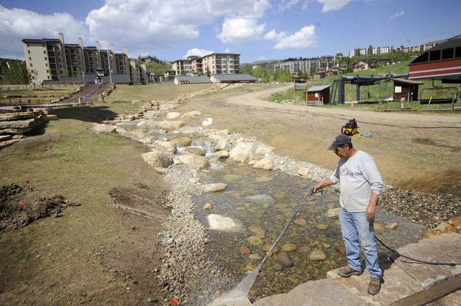 Duckels Construction worker Jose Gonzalec power washes the stone along the creek that started flowing this week at the base of Steamboat Ski Area.